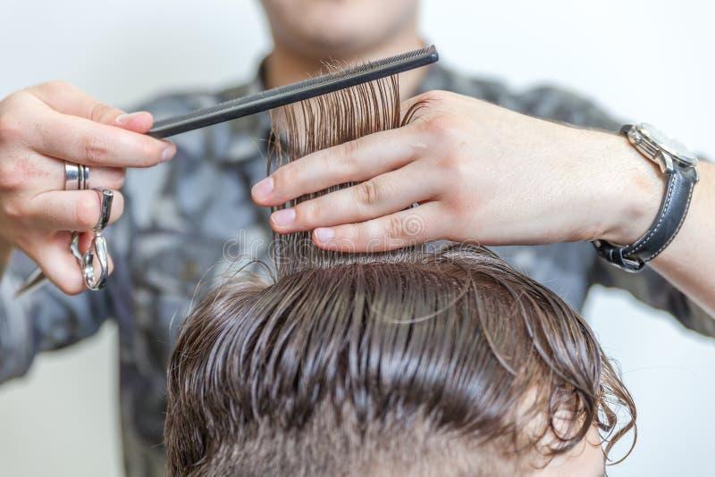 Sprawnego fryzjera tnący męski włosy zdjęcie stock
