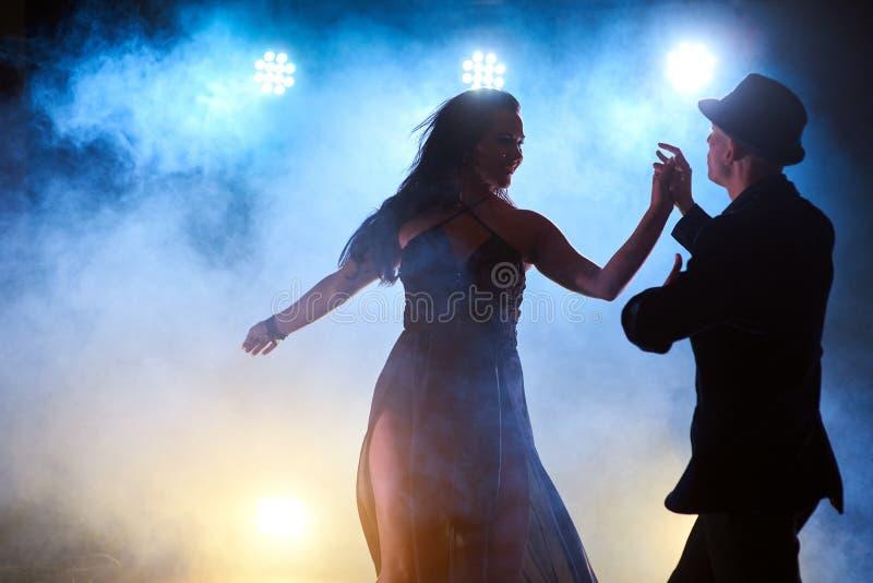 Sprawni tancerze wykonuje w ciemnym pokoju pod porozumiewają się światło i dymią Zmysłowa para wykonuje artystycznego zdjęcie royalty free