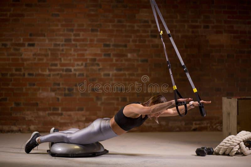 Sprawności fizycznej kobiety trening na TRX patkach w gym Crossfit styl Trenować TRX obraz royalty free