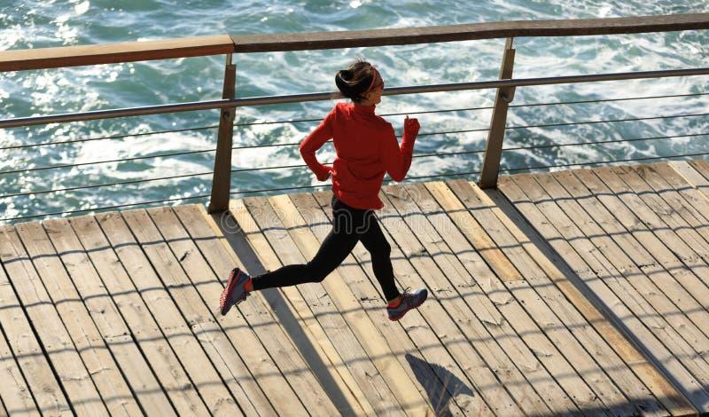 Sprawność fizyczna biegacza żeński bieg na nadmorski boardwalk obrazy stock
