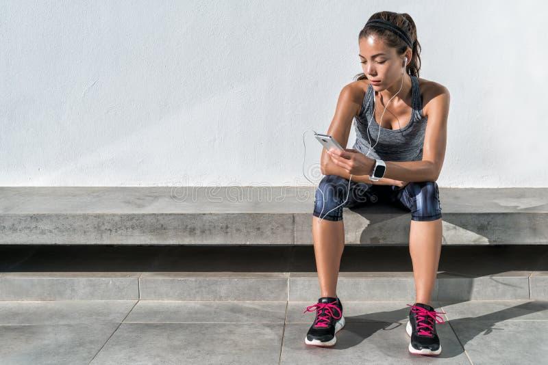 Sprawność fizyczna biegacza dziewczyna używa muzycznego telefon komórkowego app zdjęcie royalty free
