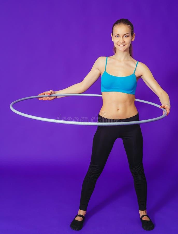 Sprawność fizyczna i gym pojęcie - młoda sporty kobieta z hula obręczem przy gym W łyżce suchy śniadanie zdjęcia royalty free