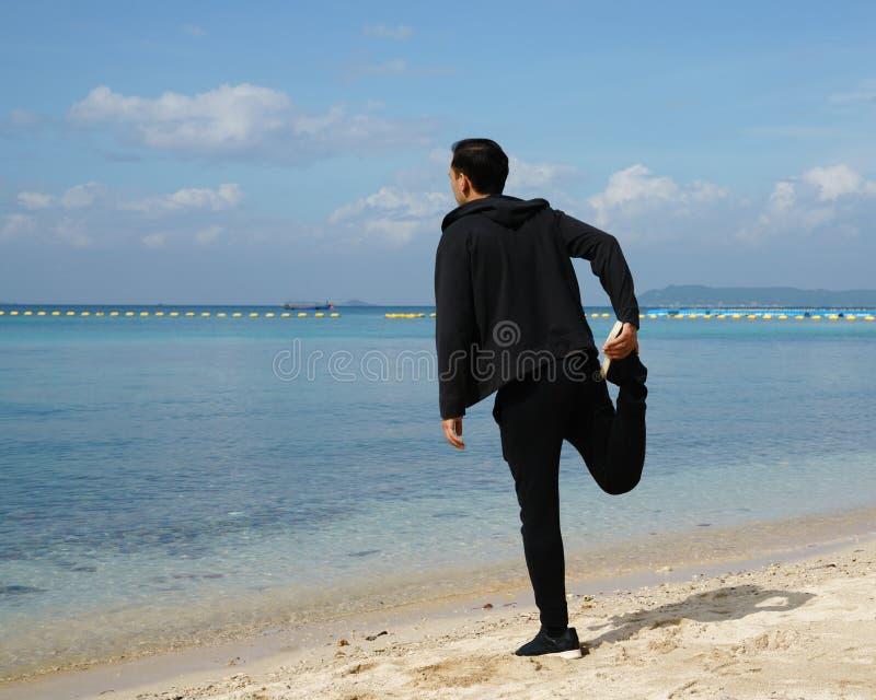 Sprawność fizyczna i zdrowy styl życia Mężczyzna robi rozciąganiu na bea zdjęcia royalty free