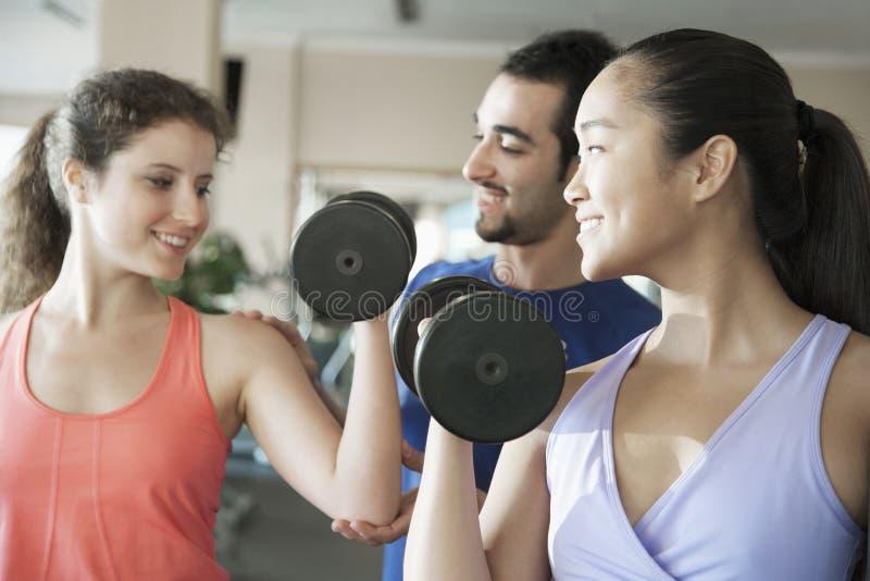 Sprawność fizyczna instruktor pomaga dwa młodej kobiety dźwignięcia ciężarom w gym obraz royalty free