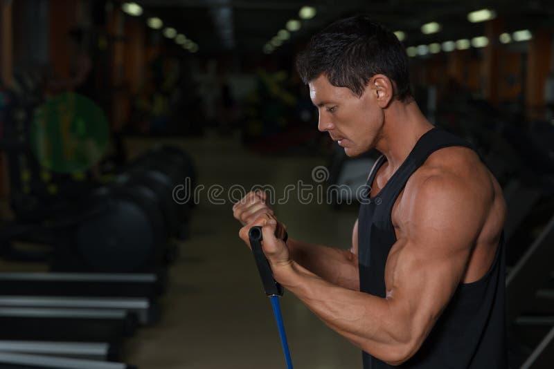Sprawność fizyczna mężczyzna ćwiczy z rozciąganie zespołem w gym Mięśniowi sporty obsługują pracującego out z gumowym zespołem obraz stock