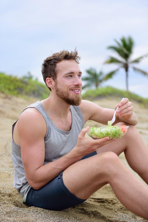 Sprawność fizyczna mężczyzna je zdrowego sałatkowego posiłek przy treningiem zdjęcie stock