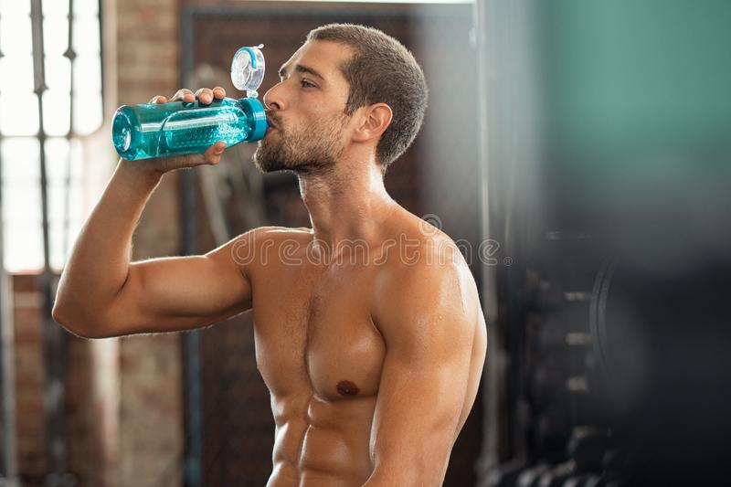 Sprawność fizyczna mężczyzna pije od bidonu zdjęcie royalty free