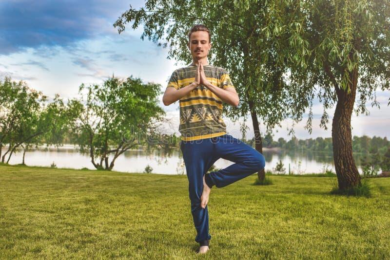 Sprawność fizyczna mężczyzna robi ćwiczeniu na jeden nodze w parku cieszyć się naturę, joga i medytacji pojęcie, Duchowe praktyki obrazy stock