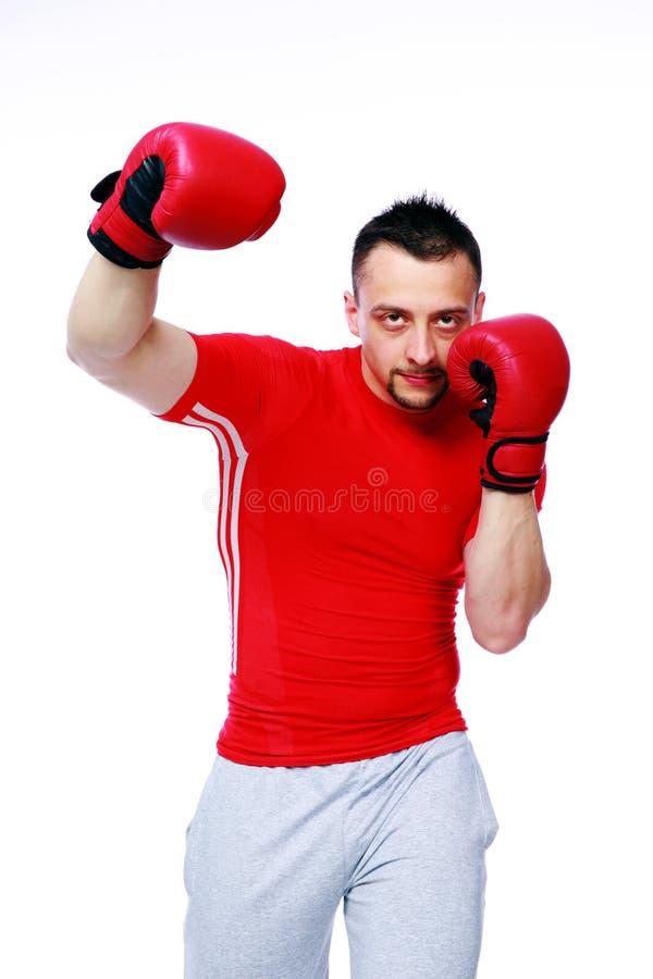 Sprawność fizyczna mężczyzna uderza pięścią z czerwonymi bokserskimi rękawiczkami obrazy royalty free