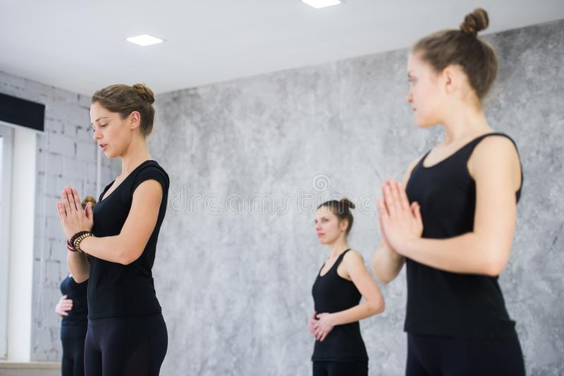 Sprawność fizyczna, medytacja i zdrowy stylu życia pojęcie, - grupa ludzi robi joga w drzewnej pozie przy studiiem obraz stock