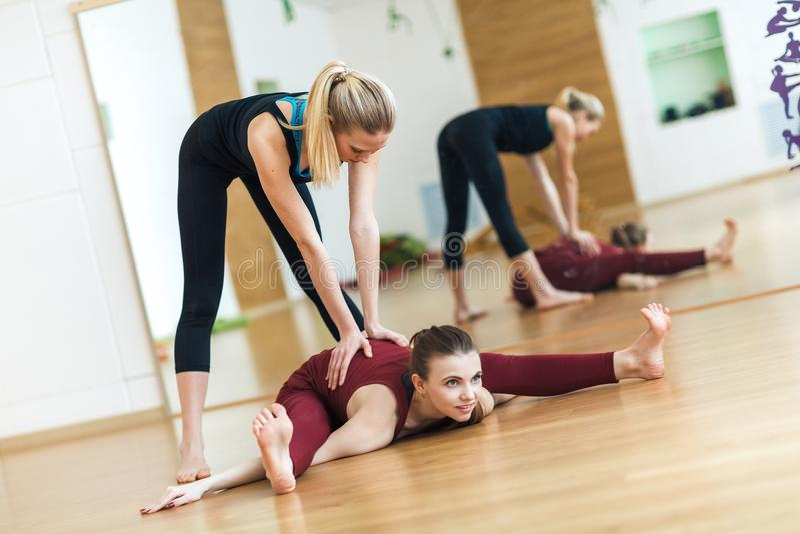 Sprawność fizyczna, rozciąga praktykę w klubie sportowym, joga nauczyciel z studencki pracującym out, instruktor pomaga żeńskiego zdjęcia royalty free