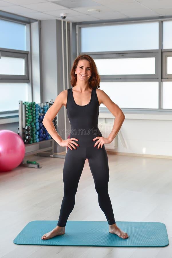 Sprawność fizyczna, sport, ćwiczy styl życia - Szczęśliwa kobieta w bodysuit pozuje na joga macie przy gym obraz stock