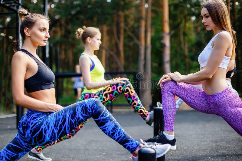 Sprawność fizyczna, sport, przyjaźń i zdrowy stylu życia pojęcie, - grupa atrakcyjne młode kobiety robi lunge outdoors zdjęcie stock