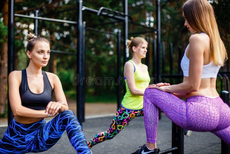 Sprawność fizyczna, sport, przyjaźń i zdrowy stylu życia pojęcie, - grupa atrakcyjne młode kobiety robi lunge outdoors zdjęcia stock