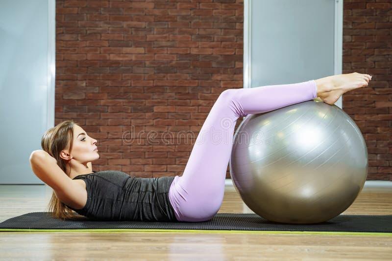 Sprawność fizyczna, sport, styl życia - młoda kobieta robi ćwiczeniom z dysponowaną piłką w pilates klasie zdjęcie stock