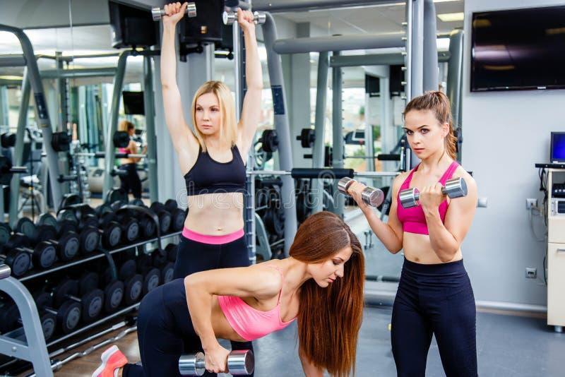 Sprawność fizyczna, sport, szkolenie, gym i stylu życia pojęcie, - grupa uśmiechnięci ludzie pracujący z dumbbells w gym out zdjęcia stock