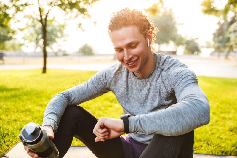 Sprawność fizyczna sportowiec w parku outdoors używa zegarka zegar zdjęcia royalty free