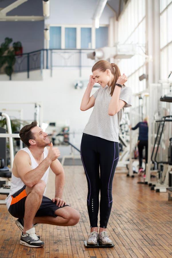 Sprawność fizyczna trener pokazuje kciuk do żeńskiego klienta zdjęcia royalty free