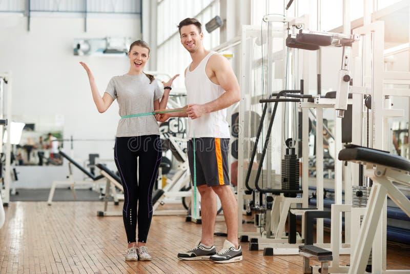Sprawność fizyczna trenera pomiarowa żeńska talia przy gym zdjęcie royalty free
