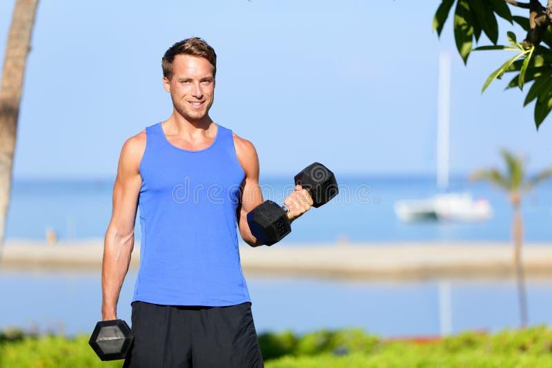 Sprawności fizycznej bicep kędzior - obciąża szkolenie mężczyzna outdoors zdjęcia royalty free