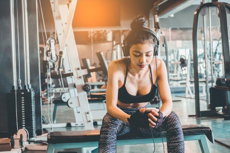 Sprawności fizycznej dziewczyna używa smartphone i hełmofony w sprawności fizycznej gym obraz stock