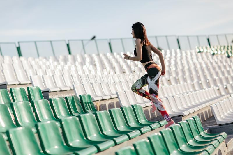 Sprawności fizycznej dziewczyna w z leggings i czerń odgórny bieg na schodkach przy stadium Kobieta treningu wellness jogging poj fotografia royalty free