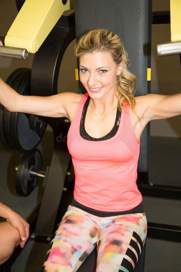 Sprawności fizycznej dziewczyna wykonuje sport z maszyną indoors przy gym obraz royalty free