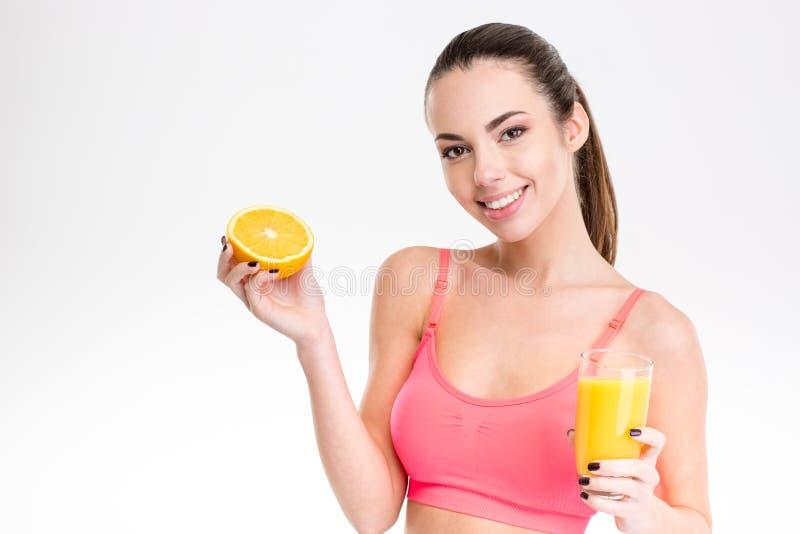 Sprawności fizycznej dziewczyna z pomarańczową połówką i szkło sok zdjęcie royalty free