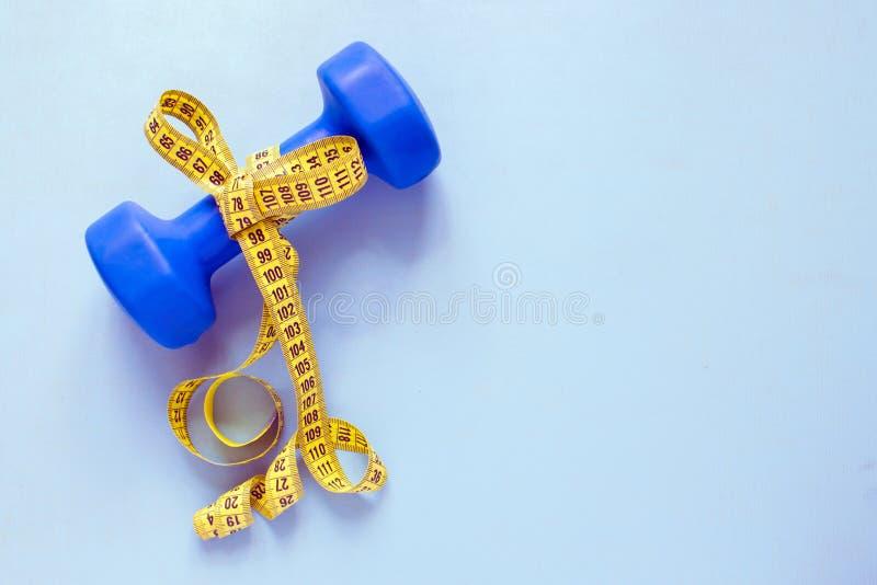 Sprawności fizycznej i ciężaru straty pojęcie Błękitny dumbbell z łękiem yello zdjęcia royalty free