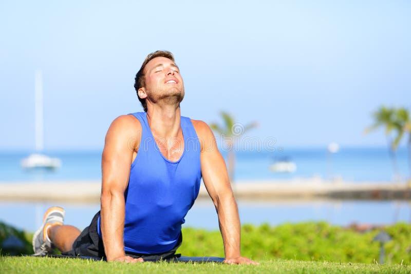 Sprawności fizycznej joga mężczyzna w kobry pozy rozciągania abs zdjęcia stock
