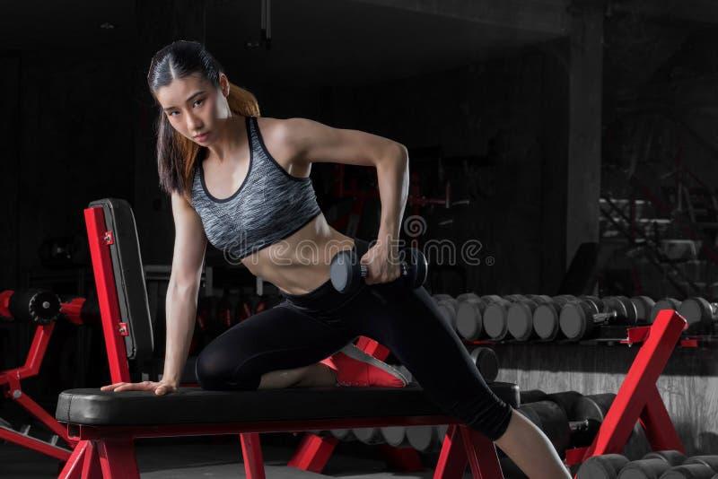Sprawności fizycznej kobieta, Azjatycka sportowa kobieta pompuje up mięśnie z dumbbells zdjęcie royalty free