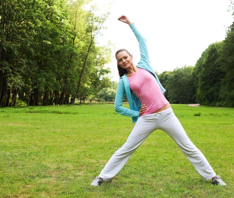 Sprawności fizycznej kobieta na zieleń parku zdjęcia royalty free