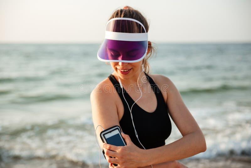 Sprawności fizycznej kobieta odpoczywa na plażowym słuchaniu muzyka z telefonem zdjęcia stock