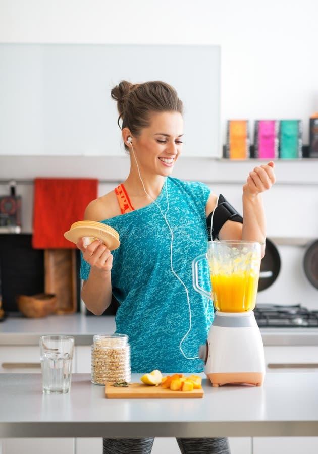 Sprawności fizycznej kobieta robi dyniowemu smoothie w kuchni zdjęcia stock