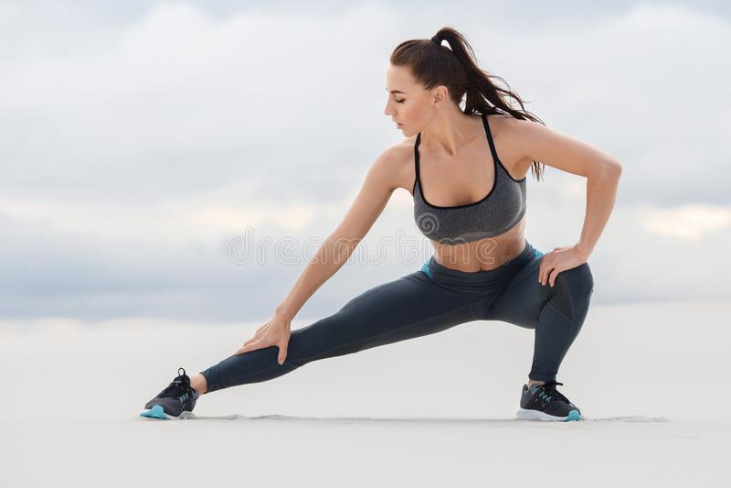 Sprawności fizycznej kobieta robi lunges ćwiczy dla noga mięśnia treningu szkolenia, plenerowy Sporty dziewczyna robi rozciągania fotografia stock