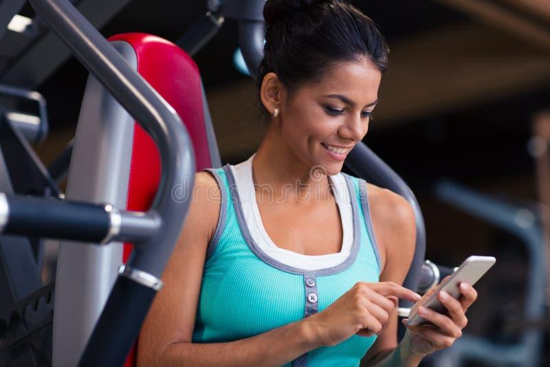 Sprawności fizycznej kobieta używa smartphone obrazy royalty free