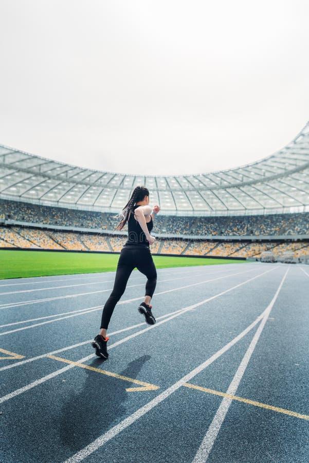 Sprawności fizycznej kobieta w sportswear bieg na bieg śladu stadium obraz stock