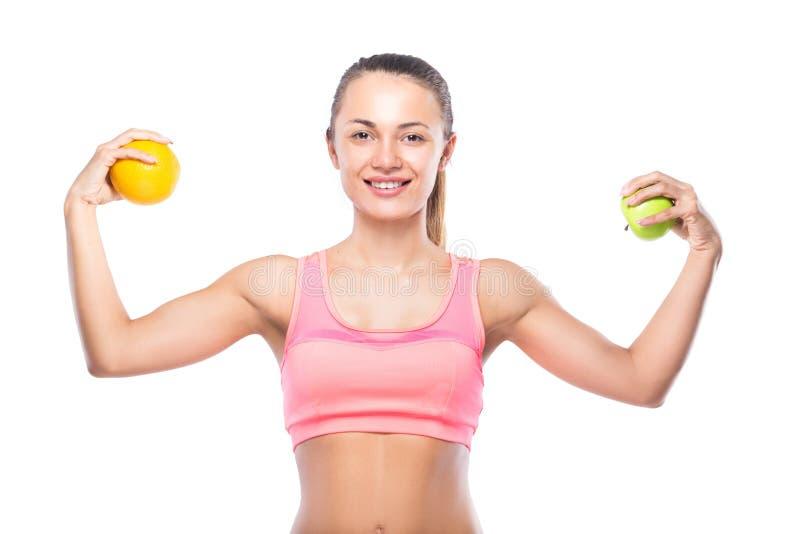 Sprawności fizycznej kobieta w sportswear z pomarańcze i jabłkiem odizolowywającymi na wh obrazy stock