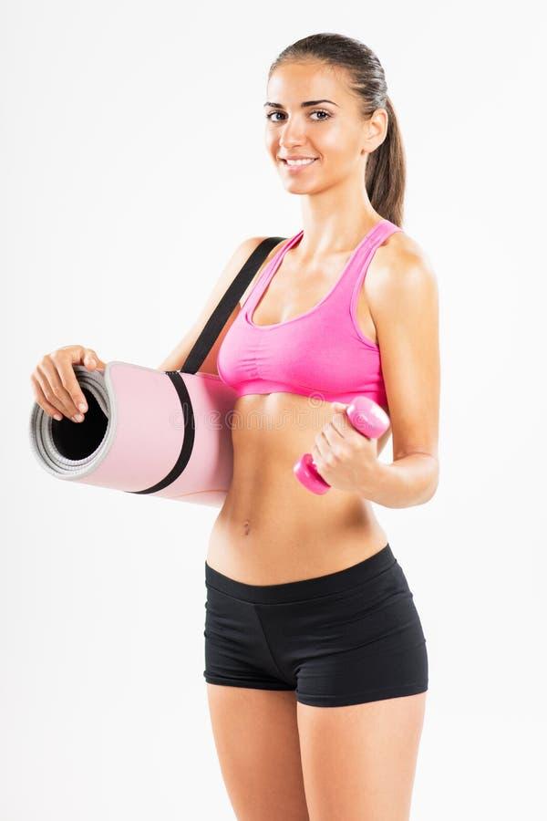Sprawności fizycznej kobieta z ćwiczeń dumbbells i matą fotografia stock