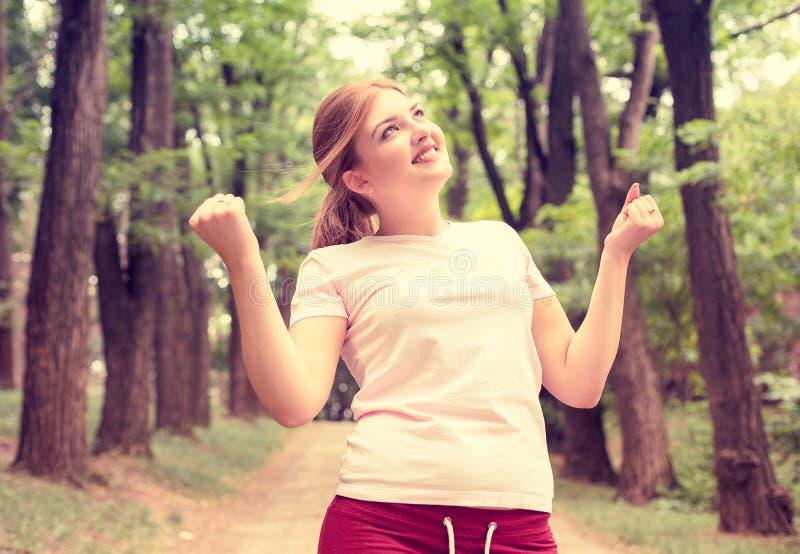 Sprawności fizycznej kobiety dźwigania ręki po pracującego out Szczęśliwa żeńska atleta na parkowym tle zdjęcia royalty free