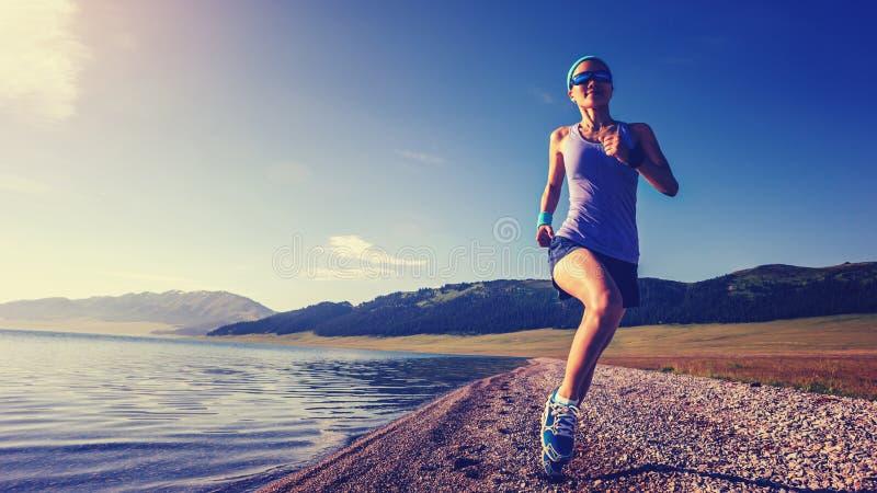 Sprawności fizycznej kobiety sporty bieg na skalistym nadmorski zdjęcia royalty free