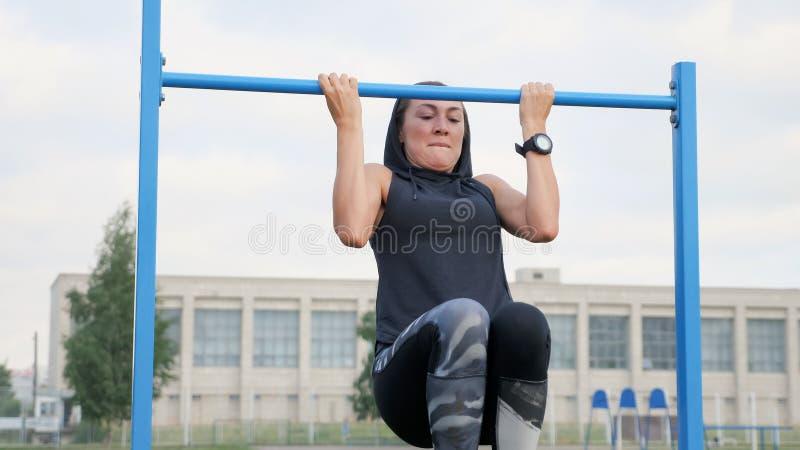 Sprawności fizycznej kobiety trening robi ćwiczeniom na horyzontalnym barze outdoors obrazy stock