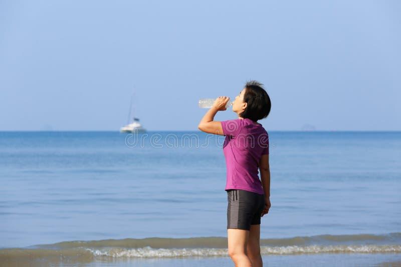Sprawności fizycznej kobiety woda pitna na plaży, Krabi zdjęcia stock