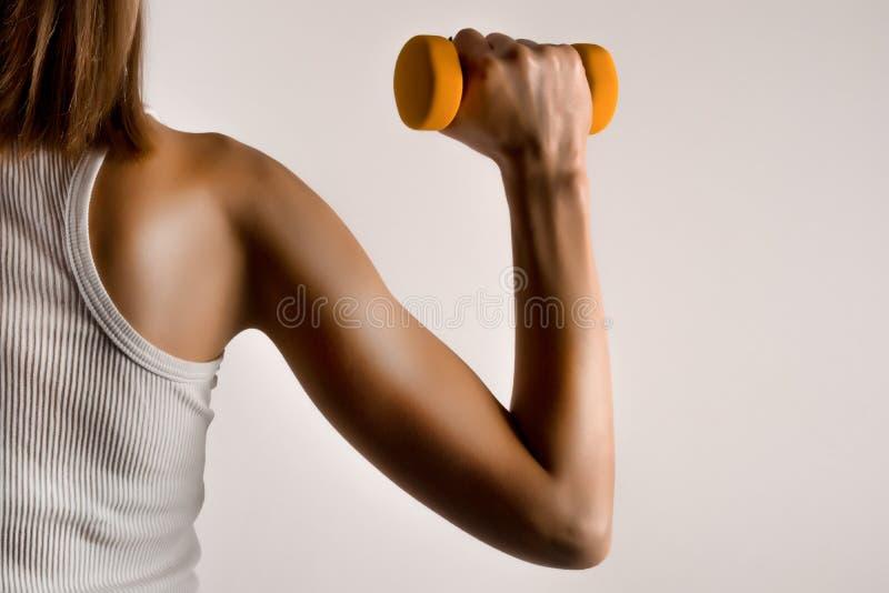 Sprawności fizycznej kobiety wzorcowa ręka z żółtym dumbbell na szarym pracownianym tle fotografia royalty free