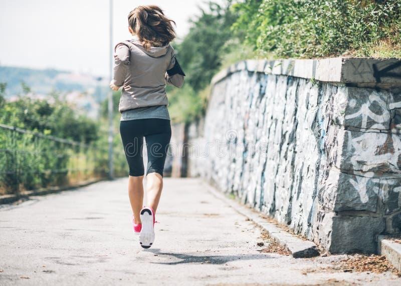 Sprawności fizycznej młoda kobieta jogging w miasto parku zdjęcie stock