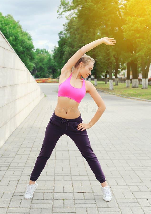 Sprawności fizycznej młoda kobieta robi rozgrzewce rozciąga ćwiczenie przed bieg, żeńską atletą przygotowywającą trening w miasto zdjęcie royalty free