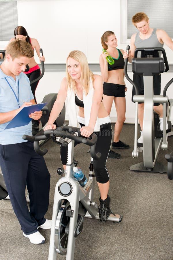 Sprawności fizycznej młode dziewczyny przy gym z instruktorem obraz royalty free