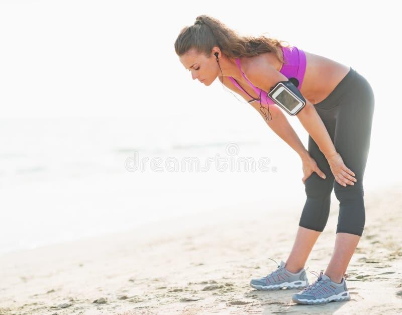 Sprawności fizycznej młodej kobiety łapanie oddycha po biegać na plaży fotografia stock