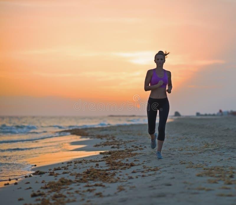 Sprawności fizycznej młodej kobiety bieg na plaży w wieczór zdjęcia royalty free