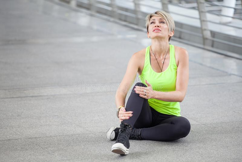 sprawności fizycznej młodej kobiety urazu nogi Działający wypadek ćwiczy na ulicie w miastowym mieście trening sporta biegacza dz fotografia stock